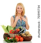 Young blond woman standing at the table with variety of fresh raw vegetables isolated on white - stock photo