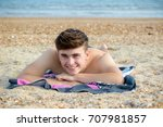 Teenage boy laying on a stoney beach - stock photo