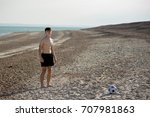 Teenage boy playing with a football on a beach - stock photo