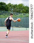 Teenage boy bouncing a basketball on a court - stock photo