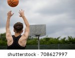 Teenage boy shooting a hoop on a basketball court - stock photo