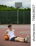 Teenage boy sitting on a  basketball court - stock photo