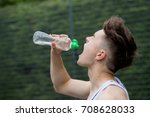 Teenage boy squirting water into his mouth - stock photo