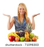 Smiling young woman standing at the table with variety of fresh fruits isolated on white - stock photo