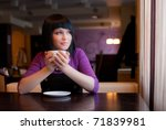 girl hold cup of coffee in hand look in window - stock photo