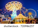 MUNICH, GERMANY - SEPTEMBER 21: people and fairground rides at the biggest folk festival in the world - the octoberfest on september 21, 2017 in munich.  - stock photo