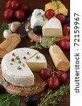 Cheese, olive and grapes on a wooden table. - stock photo