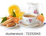 Beautiful breakfast. Green tea, eclairs, juice and fruit. - stock photo