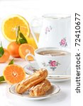 Cup of green tea, eclairs, juice and fruit. Beautiful breakfast. - stock photo
