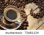 Coffee cup and grains are scattered on the wooden surface - stock photo
