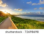 Pathway at sunset near ocean. Bright green grass with blue sky and sun. Maui Hawaii - stock photo