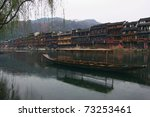China river landscape with boat and ancient building in Fenghuang county, Hunan province, China - stock photo
