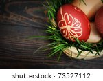 Red easter eggs in wooden basket with grass - stock photo