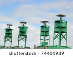 Four green navigational buoys in an industrial shipyard with a blue sky and clouds in the background - stock photo