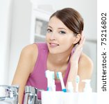 The beautiful smiling woman with clean skin face looking in mirror in a bathroom - stock photo
