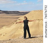 Athletic blonde girl is spreading hands wide on the edge of cliff in the Sahara desert - stock photo