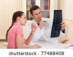 Male doctor with patient looking x-ray scan at doctor's office - stock photo