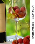 Bottle of Red wine and red fruits in glass. - stock photo