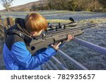 Teenage boy firing an air rifle on farmland on a cold, frosty day. - stock photo