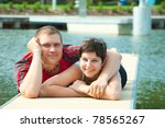 young pair on harbor pier - stock photo