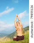 Young man is occupied yogi on the mountain - stock photo