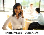 Half-length cheerful Asian businesswoman standing in foreground looking at camera, holding smartphone against head while meeting with her male coworkers defocused in background - stock photo