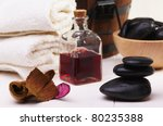spa, balanced black stones, essential oil and towel on a white table - stock photo