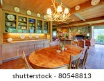 Dining room table with elk chandelier light above it. - stock photo