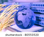 globe with network cables and servers in a technology data center - stock photo