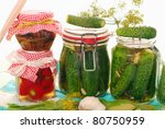 jars of homemade preserves of cherry pepper,mushrooms and pickled cucumbers isolated on white - stock photo