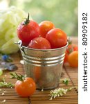 Cherry tomatoes in a bowl with basil.  Selective focus, shallow doff - stock photo