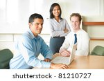 Latino businessman leader sitting at desk on laptop in conference room, meeting with diverse team of business people, attractive Asian woman and Caucasian male looking at camera. Horizontal - stock photo