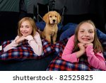 two kids and a puppy camping in a tent with sleeping bags. - stock photo