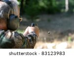 an unidentifiable person shoots a high power pistol. low depth of field photo so the background in out of focus and focus is on the gun and shell casing in the air. - stock photo