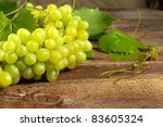 bunch of grapes with leaves on the old wooden texture - stock photo