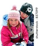 Boy and girl having fun in the fresh white snow - stock photo