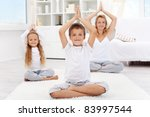 Happy balanced life - woman and kids doing yoga exercise at home - focus on boy - stock photo