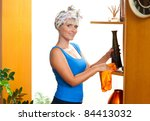 attractive housewife dusting her home - stock photo