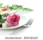 pink rose and chocolate candy on a white plate - stock photo