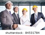 Business people in hard hats looking up at the site - stock photo
