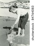 Vintage photo of young girl on beach (fifties) - stock photo