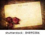old postcard with dried roses and grunge texture - stock photo