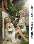 Two beauty ladies with cute puppies - stock photo