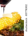 Steak dinner with corn on the cob and a glass of red wine. - stock photo