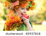 Woman with maple leaves outdoors. Close up face. - stock photo
