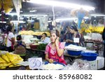 BANGKOK, THAILAND - MARCH 25: Seller using her smartphone at local market in Bangkok Chinatown on March 25, 2011 in Bangkok, Thailand. Bangkok  Chinatown is popular tourist attraction and a food haven - stock photo