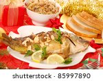 whole carp baked with flaked almonds served with sauerkraut (bigos) and bread on  christmas table - stock photo