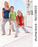 People exercising at home - woman with her kids stretching - stock photo