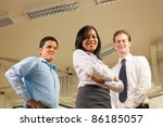 Ambitious Asian woman arms crossed looking down smiling in front of diverse business team standing, looking down at the camera at a low angle where white office ceiling visible. Horizontal copy space - stock photo
