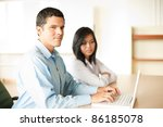 Ambitious Hispanic professional man sitting at office conference room desk, smiling, looking at camera, typing at laptop, leading one on one meeting with Asian coworker looking down at screen - stock photo